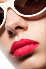 A woman's face close up in sunglasses and red lips