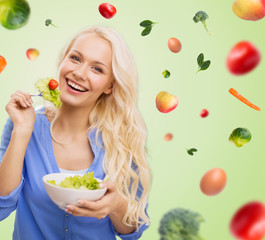 smiling young woman eating green vegetable salad
