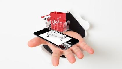 Composite image of open hand bursting through paper