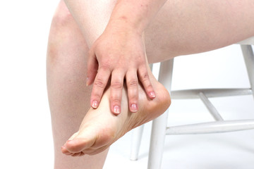 damaged foot problems, neglected. Dermatologist examining a foot for callus and dry skin, towards white