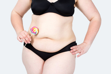 Woman showing her fat body and holding a lollipop. Healthy lifestyles concept and diet.