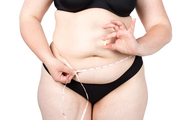 Woman showing her fat body and holding a tablets. Healthy lifestyles concept and diet. Obese neglected body isolated over white background.
