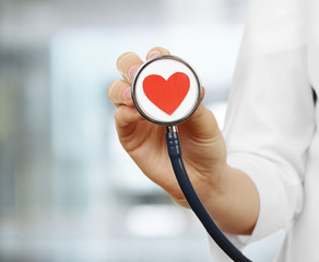 Stethoscope with heart in doctor hand, close up