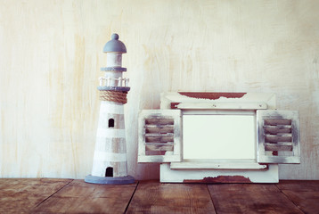 Old vintage wooden white frame and lighthouse on wooden table