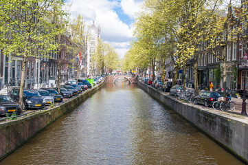 Amsterdam canal with parked cars along the bank. Netherlands.