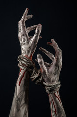 Hands bound,bloody hands, mud, rope, on a black background