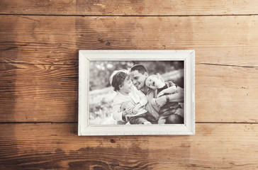 Picture frame with family photo laid on a wooden background.
