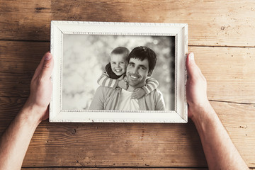 Picture frame with family photo on a wooden background.