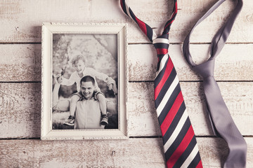 Picture frame with family photo and ties on wooden background.