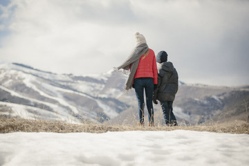 A brother and sister standing side by side in the snow, back view.