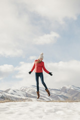 A young girl with long legs and red jacket, leaping in the air above the snow