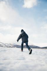 A boy running away across the snow.