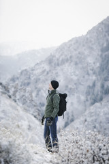 A man hiking through the mountains carrying a rucksack.
