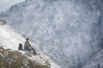 A man, a hiker in the mountains, taking a rest on a rock outcrop above a valley.