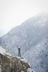 A man greeting the sun, with his arms raised on a rock outcrop in the mountains.