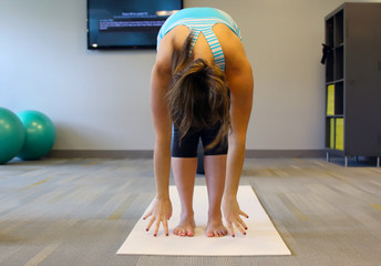 Female yoga excersise on a white mat