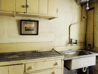 An old fashioned kitchen sink and cupboards.