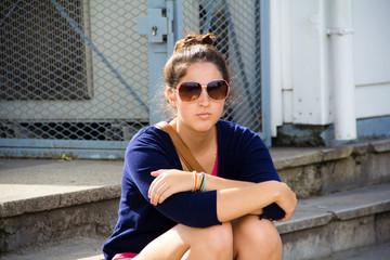 Woman wearing sunglasses sitting on a step