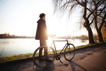Teenager (14-15) standing with bicycle by river