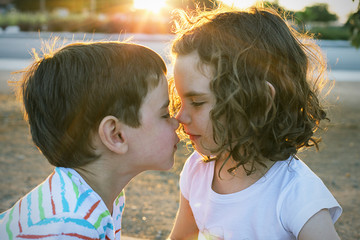 Girl and boy rubbing noses outdoors