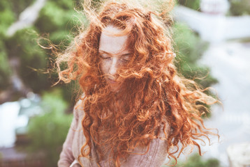 Portrait of young woman with long, curly red hair