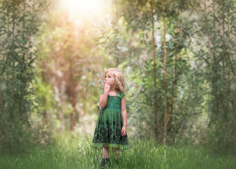 Girl (4-5) standing in woodland