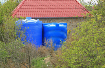 Blue water tank on the tower in park