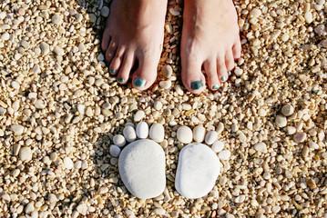 Croatia, Stones in shape of feet in front of woman's feet Fototapete