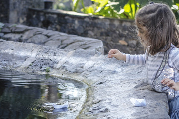 Girl sailing paper boats in fountain