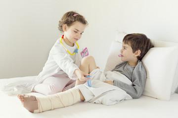 Brother (4-5) and sister (6-7) playing patient and nurse