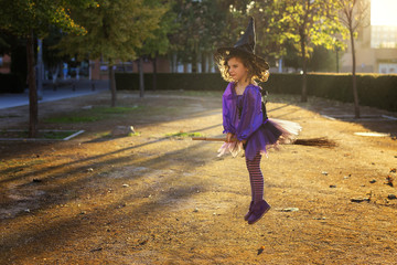 Girl (6-7) playing witch flying on broomstick