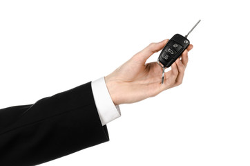 car salesman in a black suit holding a car key isolated