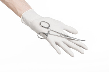 doctor's hand in a white glove holding a surgical clip isolated