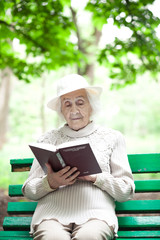 portrait of  happy grandmother on a park bench, read book