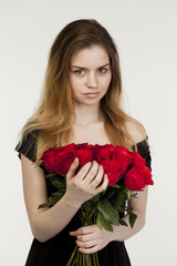 Portrait of a young beautiful girl with a bouquet of red roses