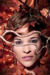 Hübsche junge Frau im Herbstlaub liegend