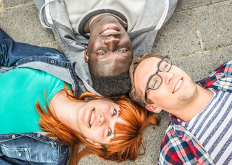 three mixed race friends lying on the ground
