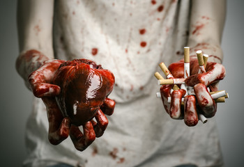 bloody hand holding a cigarette smoker and bloody human heart