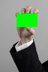 businessman in a black suit and black tie holding a green card