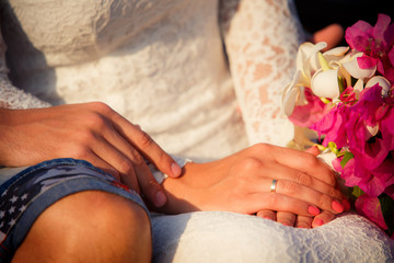bride and groom hands  with bouquet