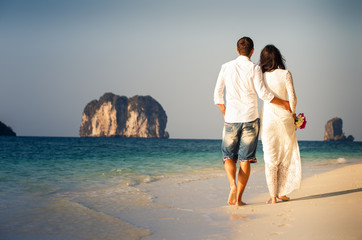 bride and groom walk barefoot on beach