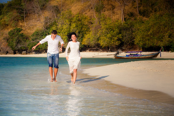 brunette bride and groom run in shallow sea