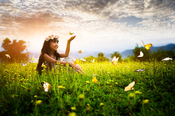 Little asian girl in garden with hands up and butterflys