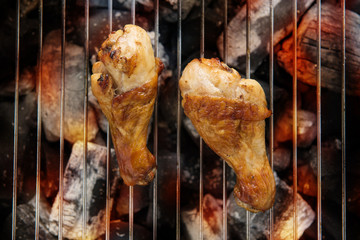 Chicken legs grilling over flames on a barbecue.