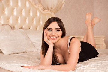 beautiful girl in peignoir lying on a luxury bed with cushions a