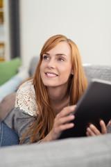 entspannte junge frau mit tablet-pc zuhause auf dem sofa