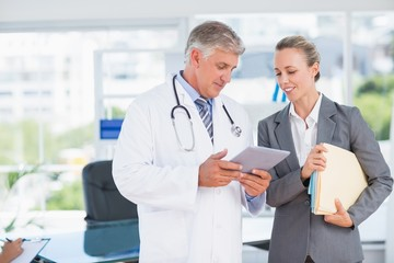 Confident doctor and pretty businesswoman discussing