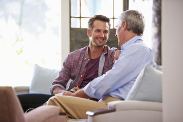 Senior Father With Adult Son Relaxing On Sofa At Home