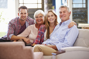 Family With Adult Children Relaxing On Sofa At Home Together