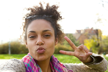 Cute girl making fun face with peace sign